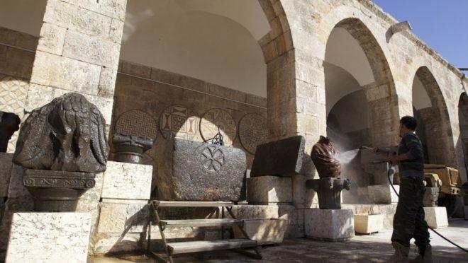 مقاتل من الجيش السوري الحر يغسل تماثيل في متحف معرة النعمان في إدلب - انترنت