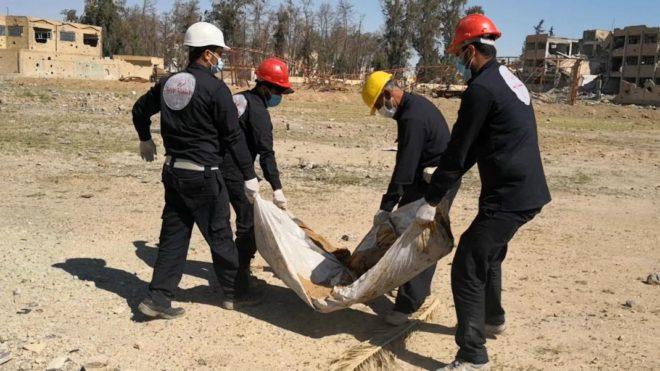أعضاء فريق الاستجابة الأولية في مدينة الرقة في سوريا ينتشلون جثة من مقبرة جماعية في ملعب الرشيد. © 2018 هيومن رايتس ووتش